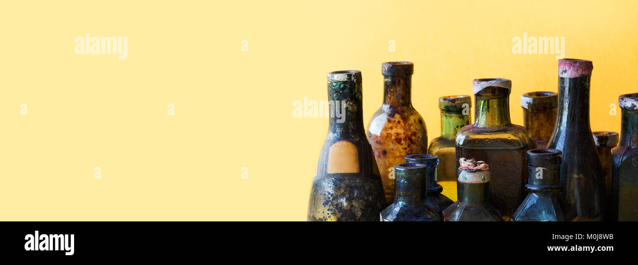 Vintage bottles close-up. Colorful dirty glass flacon set. Soft yellow background, shallow depth of field. copy - Stock Image