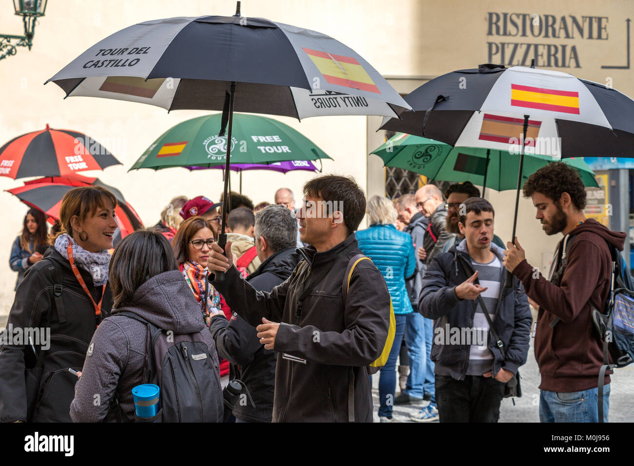 Tour guides near Prague Old Town Square tout for business from tourists and visitors by holding aloft coloured umbrellas - Stock Image