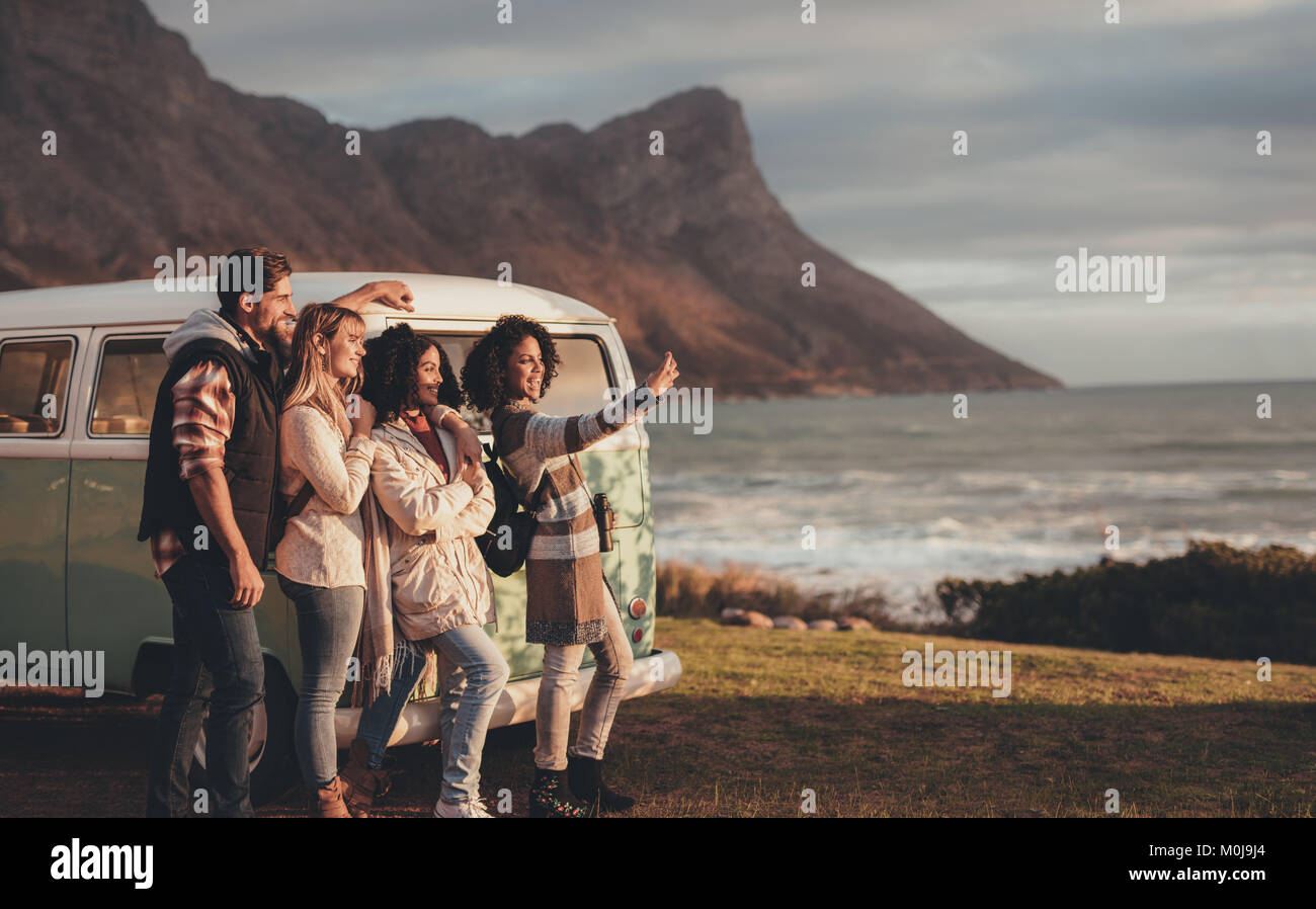 Friends on road trip taking self portrait with mobile phone by the minivan. Group of man and women together making - Stock Image