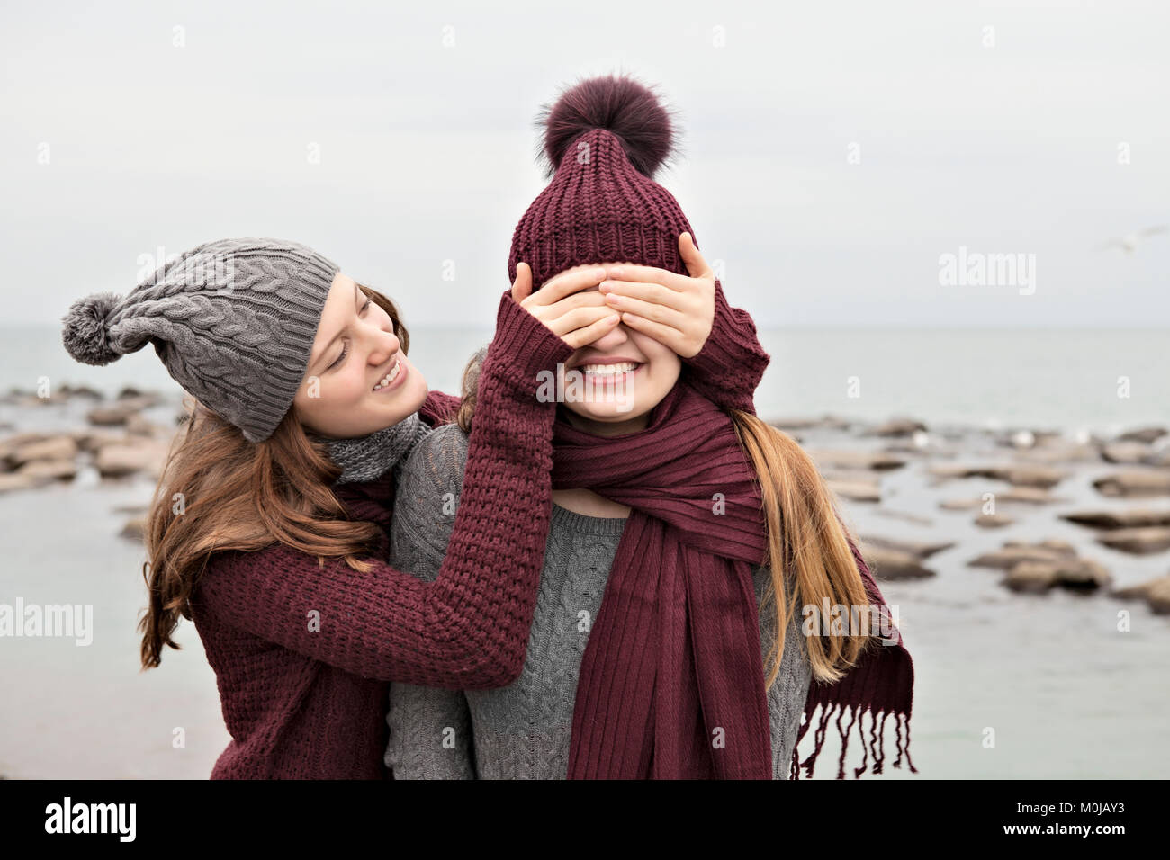 Two friends playing on the beach wearing knit hats and scarves, Woodbine Beach; Toronto, Ontario, Canada - Stock Image