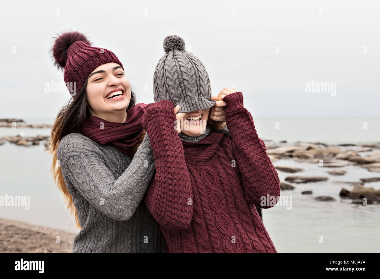 e78b37f4229 Two friends playing on the beach wearing knit hats and scarves Stock ...