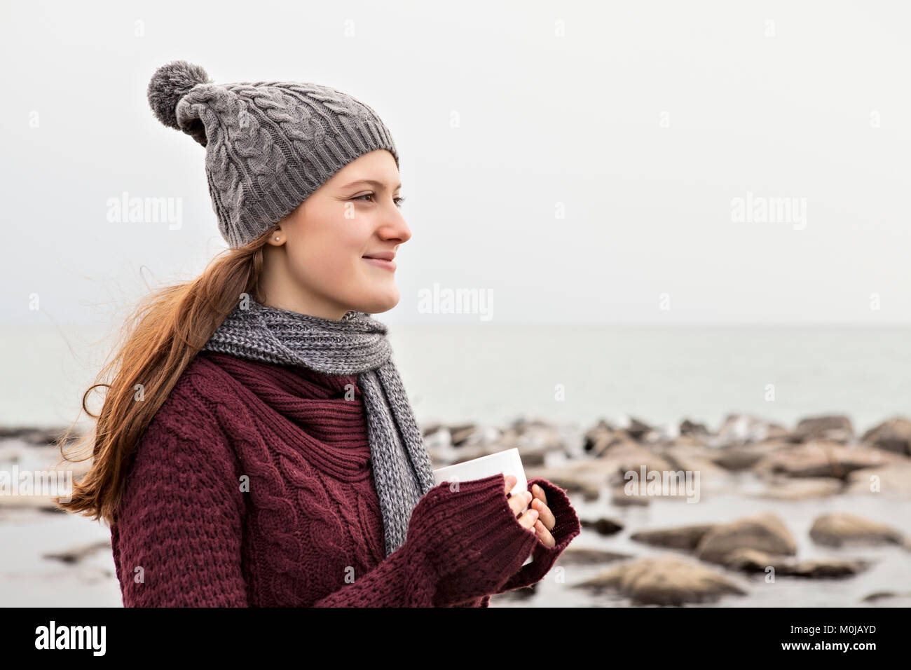 Girl standing on a beach in autumn holding a mug and wearing a knit hat and scarf, Woodbine Beach; Toronto, Ontario, - Stock Image