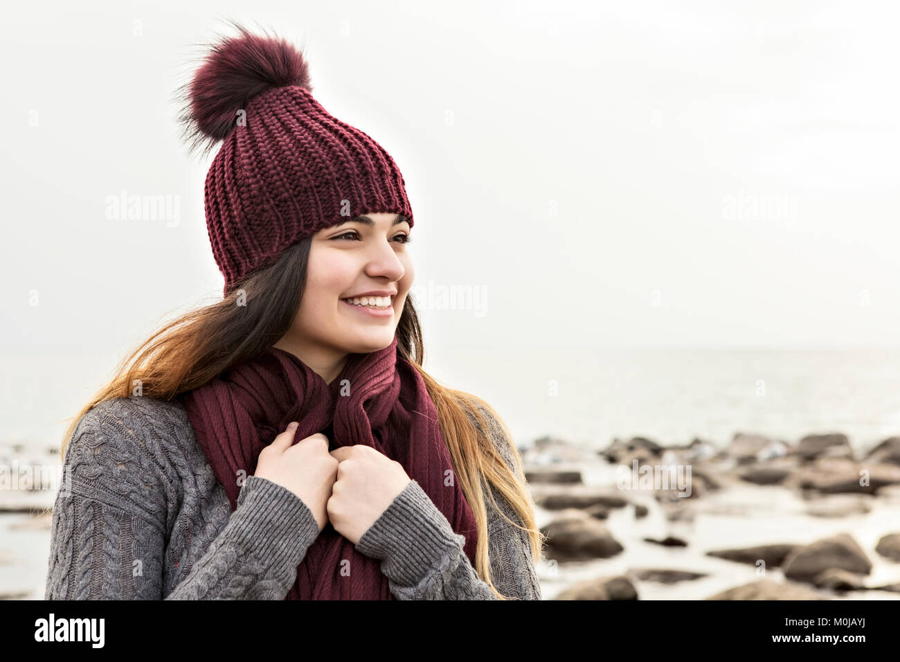 Girl standing on a beach in autumn wearing a knit hat and scarf, Woodbine Beach; Toronto, Ontario, Canada - Stock Image