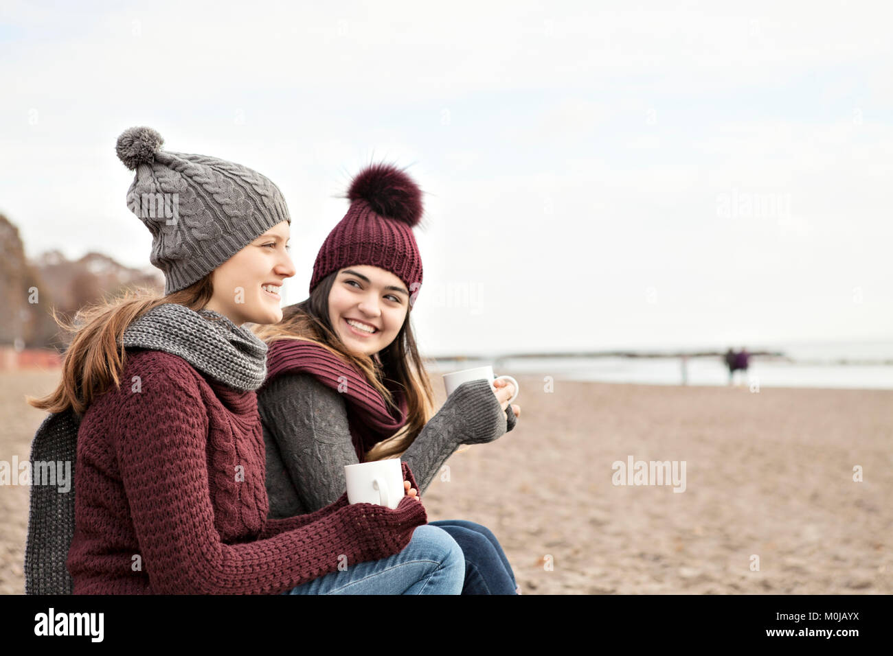 30c4a3a0b69 Two friends at the beach wearing knit hats and scarves, sitting and ...