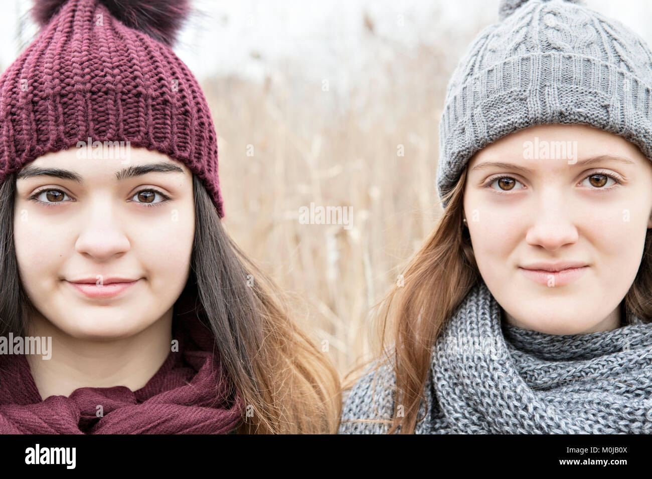 Two teenage girls wearing knit hats and scarves and looking at the camera; Scarborough, Ontario, Canada - Stock Image