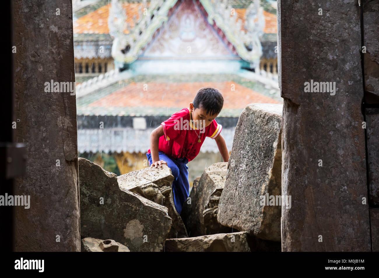 Young boy climbing in the ancient Angkorian temple at Wat Ek Phnom; Battambang, Cambodia - Stock Image