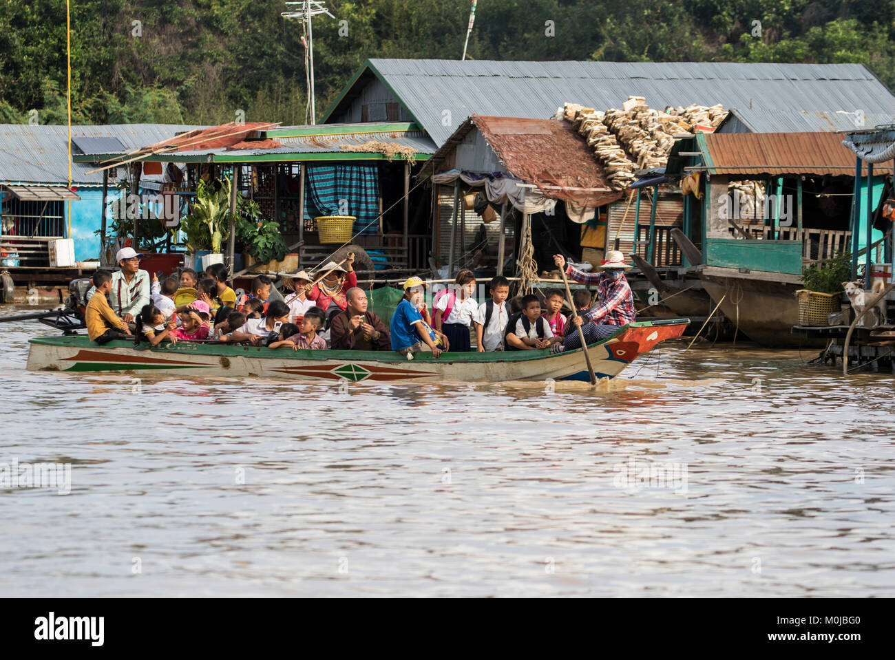 People in a public boat by a floating village in the Tonle Sap; Siem Reap, Cambodia Stock Photo