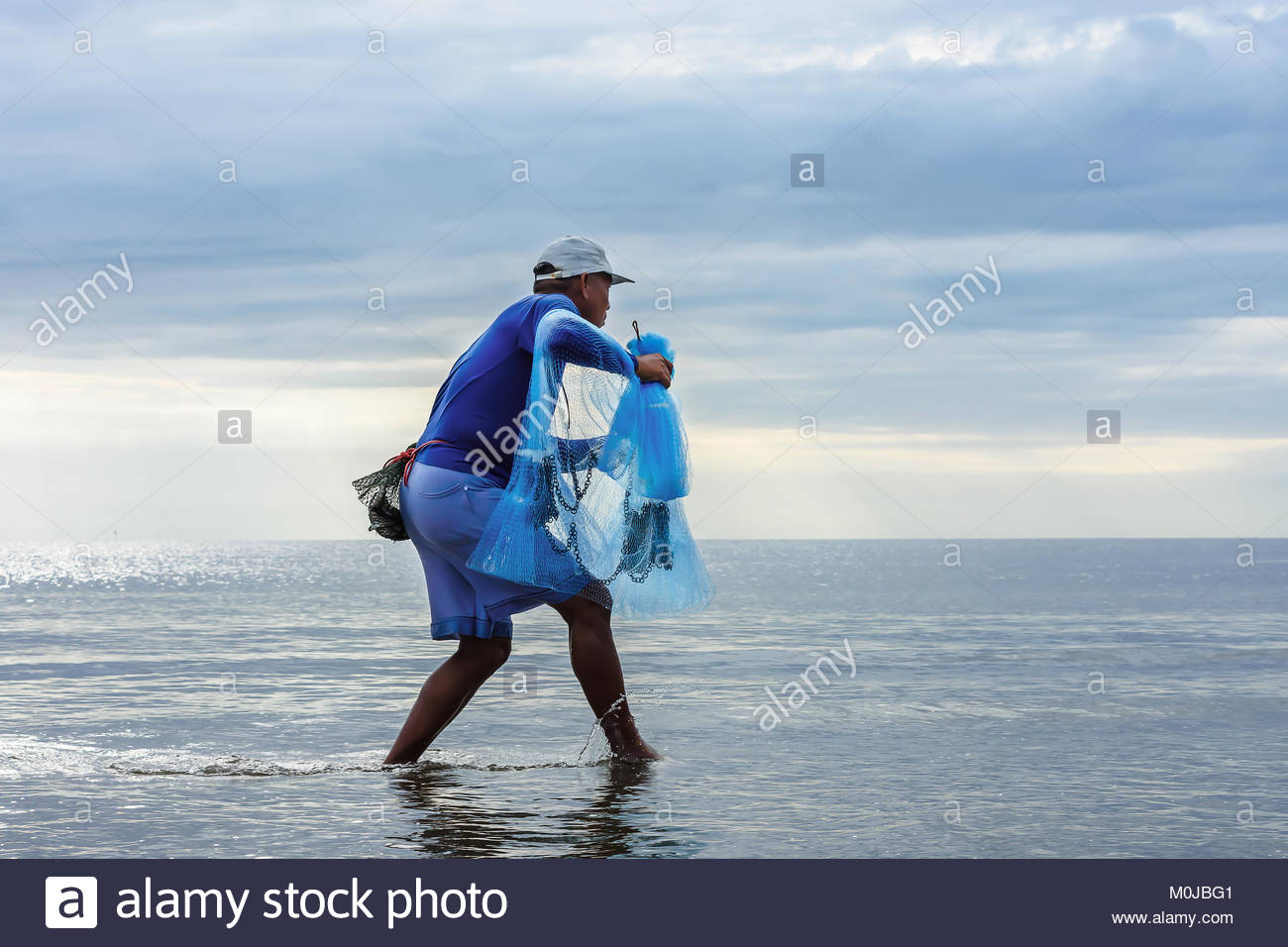 Thai fisherman got ready for a fish catch in the net - Stock Image