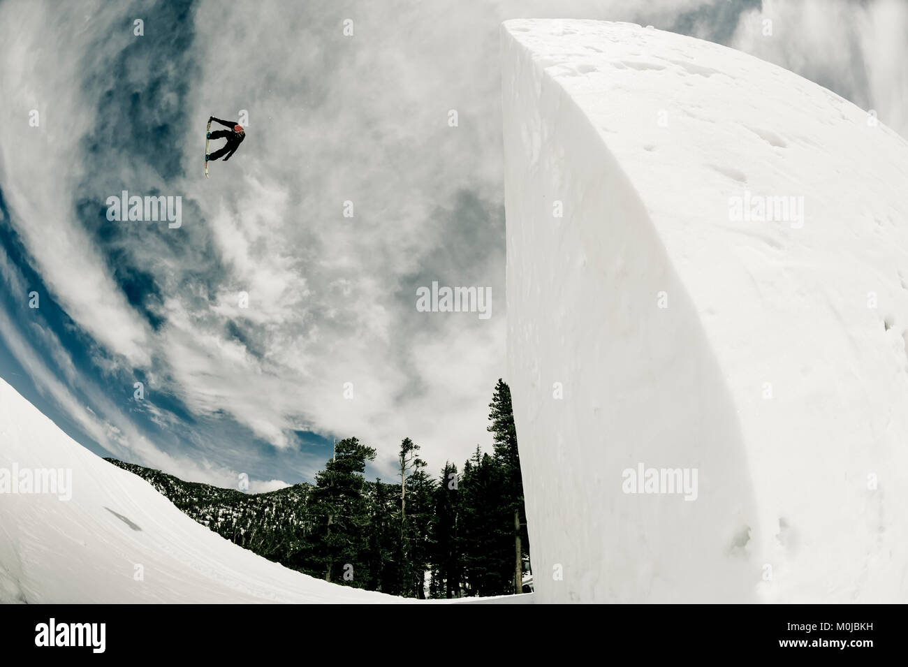 A professional snowboarder flipping mid-air at Heavenly Resort; South Lake Tahoe, California, United States of America Stock Photo