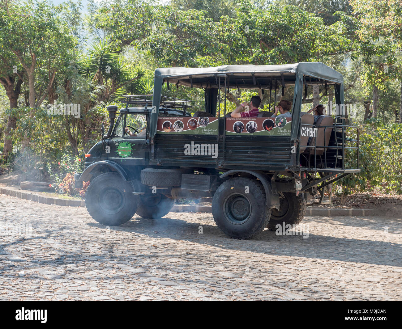 Tourists Aboard An Open Sided Truck On A Guided Tour From The Filadelfia Coffee Plantation And Resort Antigua Guatemala - Stock Image