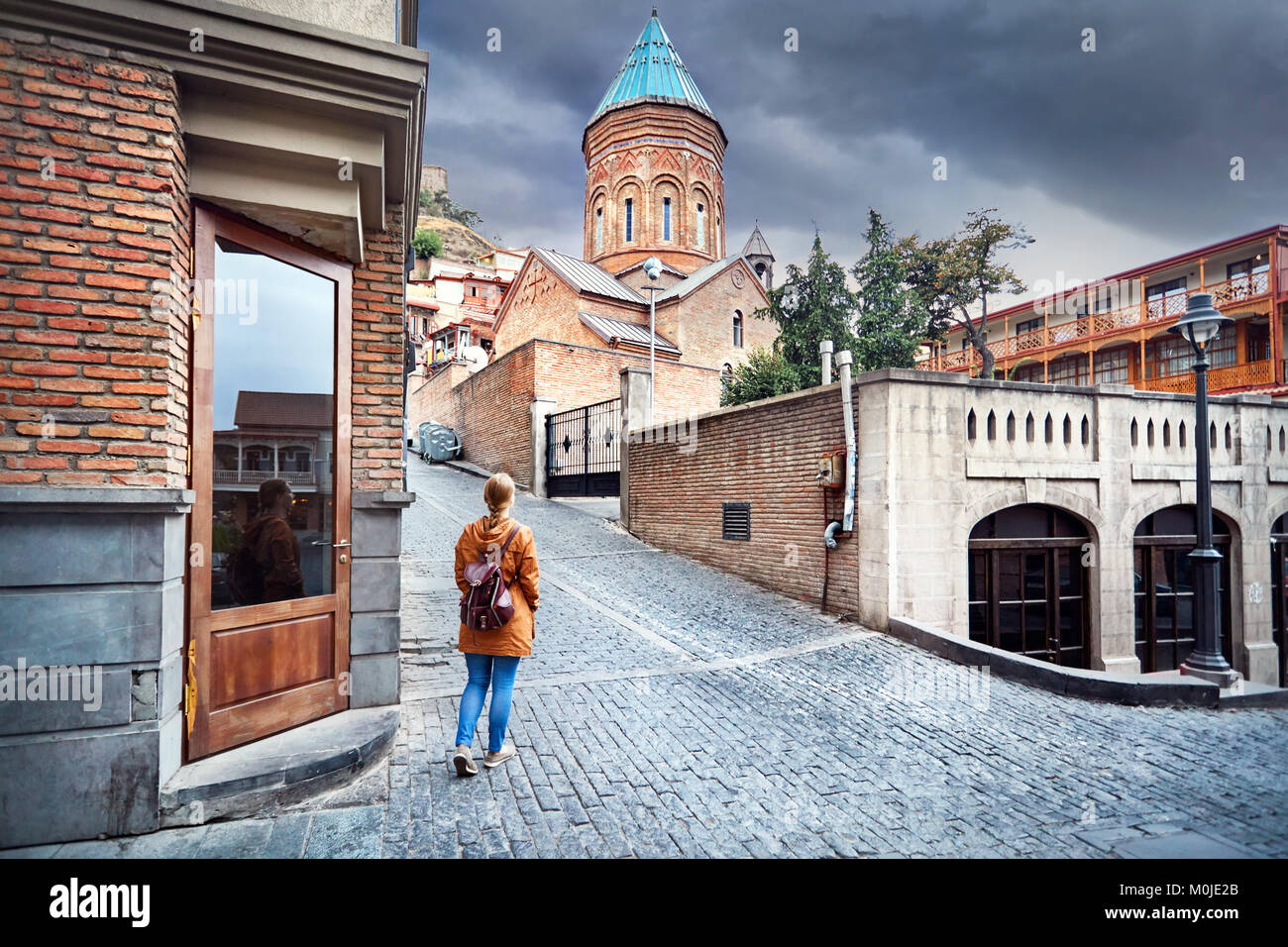 Tourist woman in brown jacket walking down the Old streets near church in central Tbilisi, Georgia - Stock Image