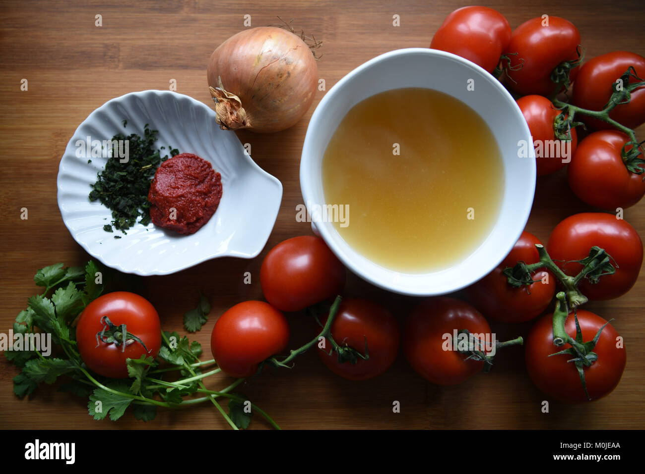 overhead food photography view of ingredients for home made tomato soup on a rustic wood board background with vegetables - Stock Image