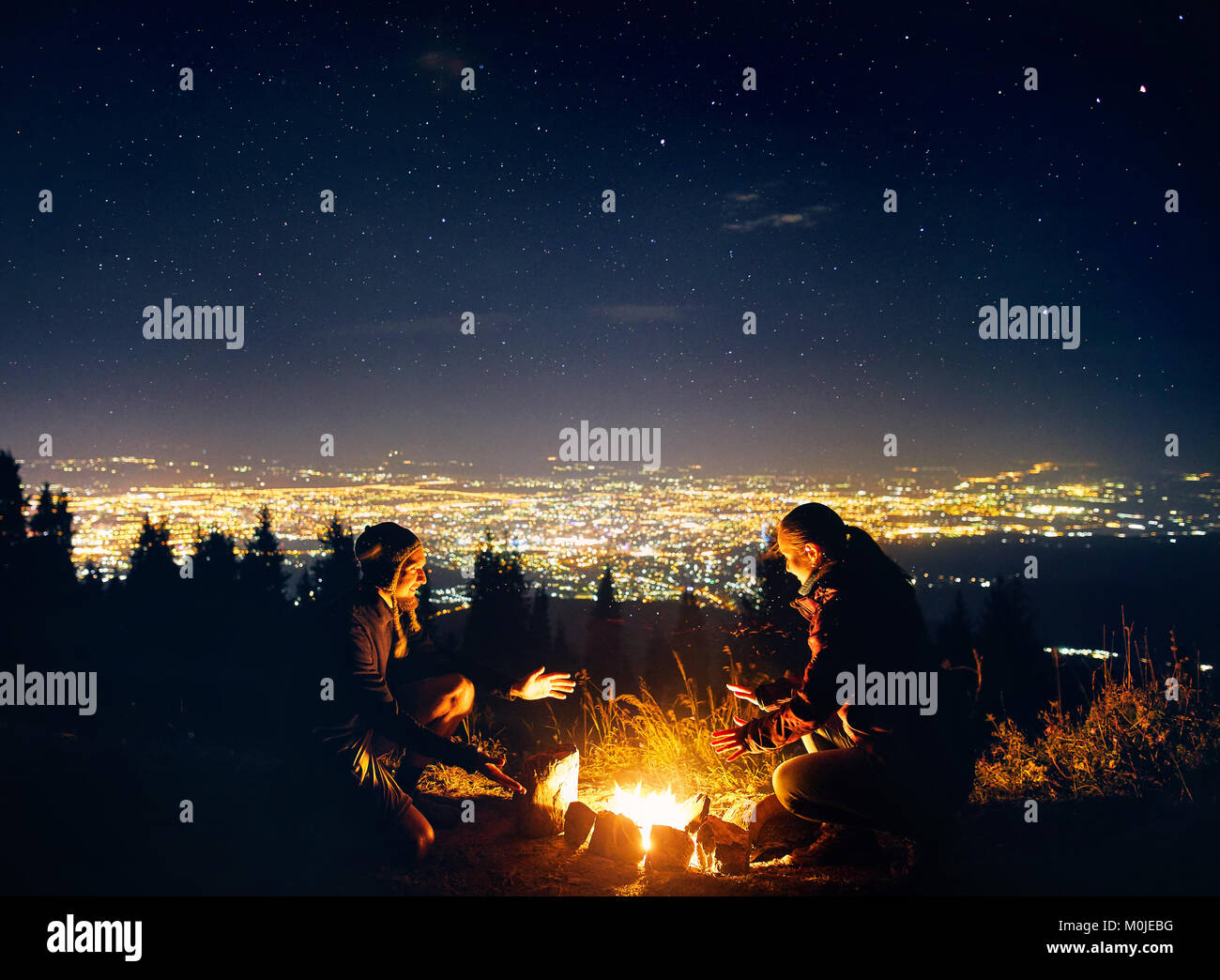 Happy couple hikers warm they hands near campfire under night sky with stars and city lights at background - Stock Image