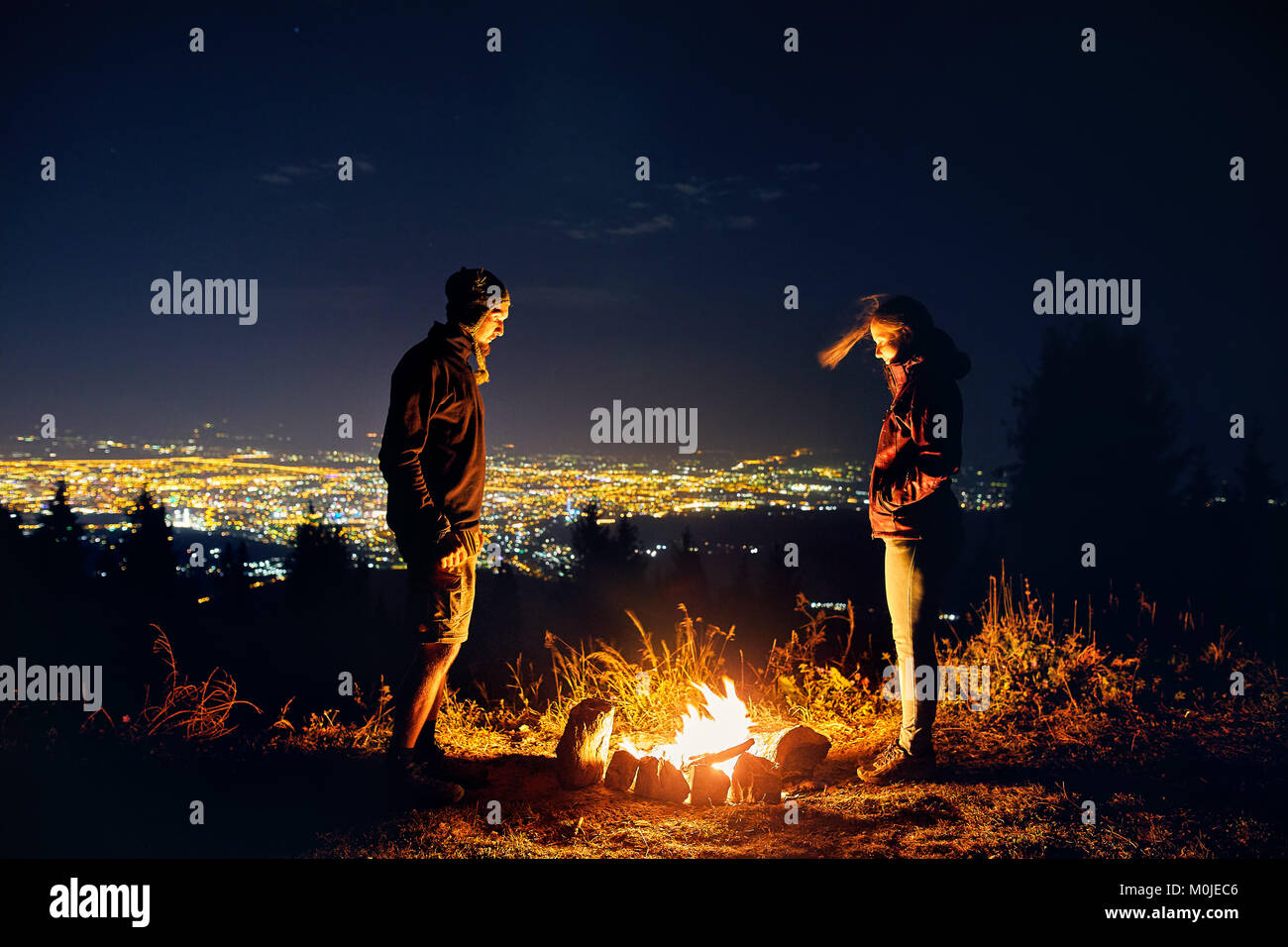 Happy couple hikers near campfire under night sky and city lights at background - Stock Image