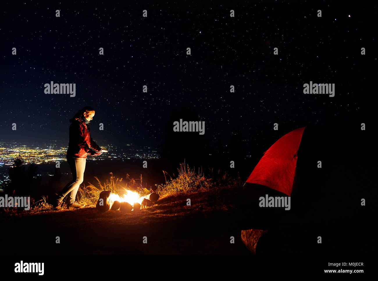 Beautiful hiker girl warm her hands near campfire under night sky with stars and city lights at background. - Stock Image
