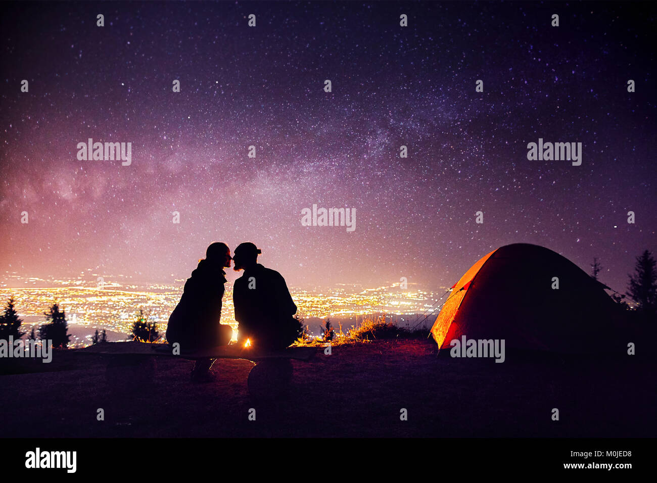 Happy couple in silhouette kissing near campfire and orange tent. Night sky with Milky Way stars and city lights - Stock Image
