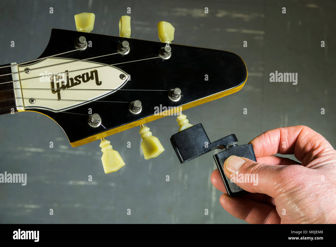 Gibson Flying V electric guitar headstock, with a man's fingers holding a string winder against a tuning peg / tuner, - Stock Image