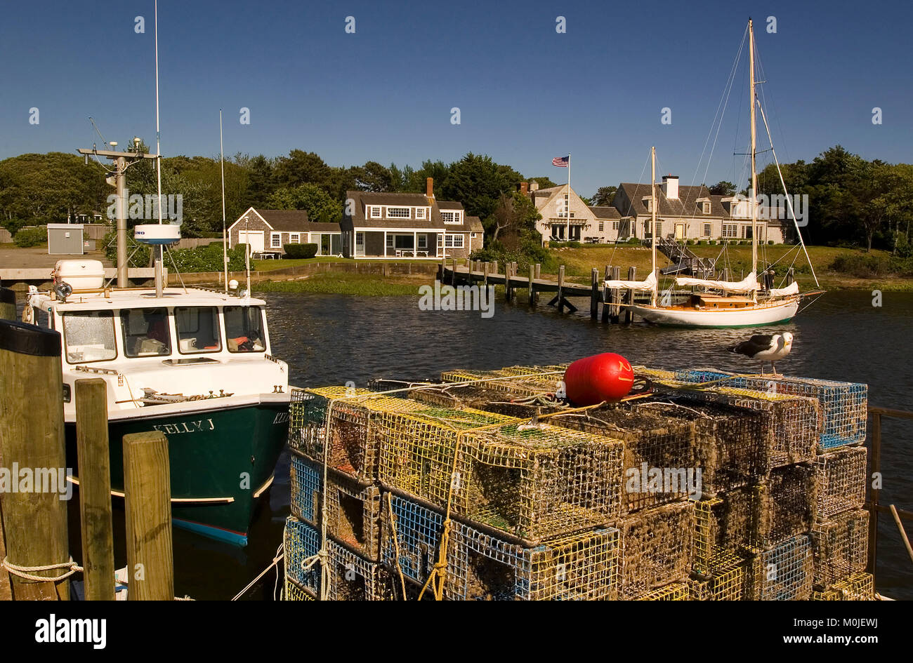Lobster traps and a fishing boat along with a private yacht and upscale home in Whychmere Harbor, Harwich Port, - Stock Image