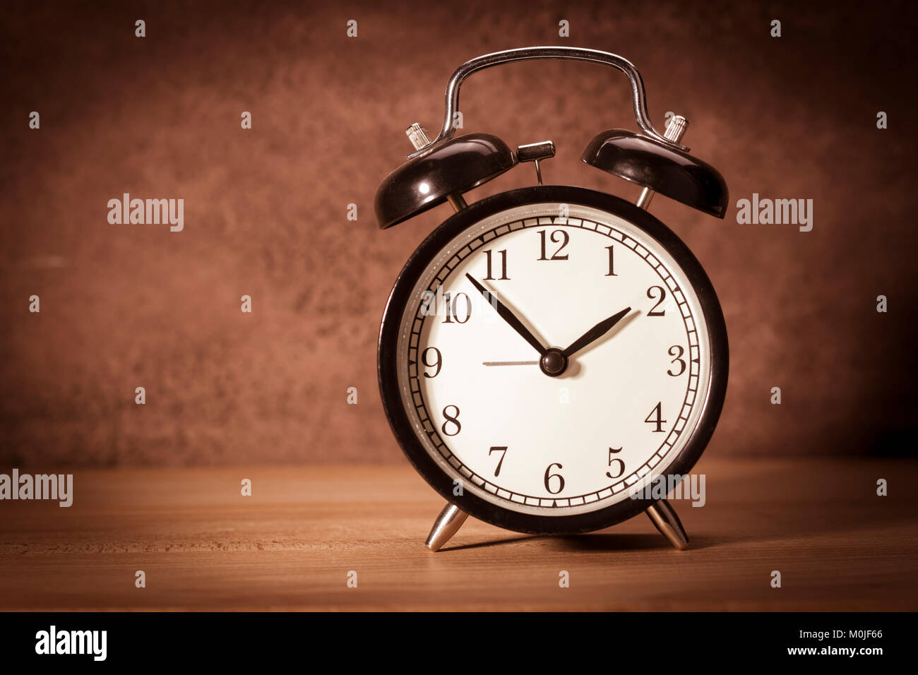 Clock - Vintage old alarm clock on sackings and a wooden background. Toned Stock Photo