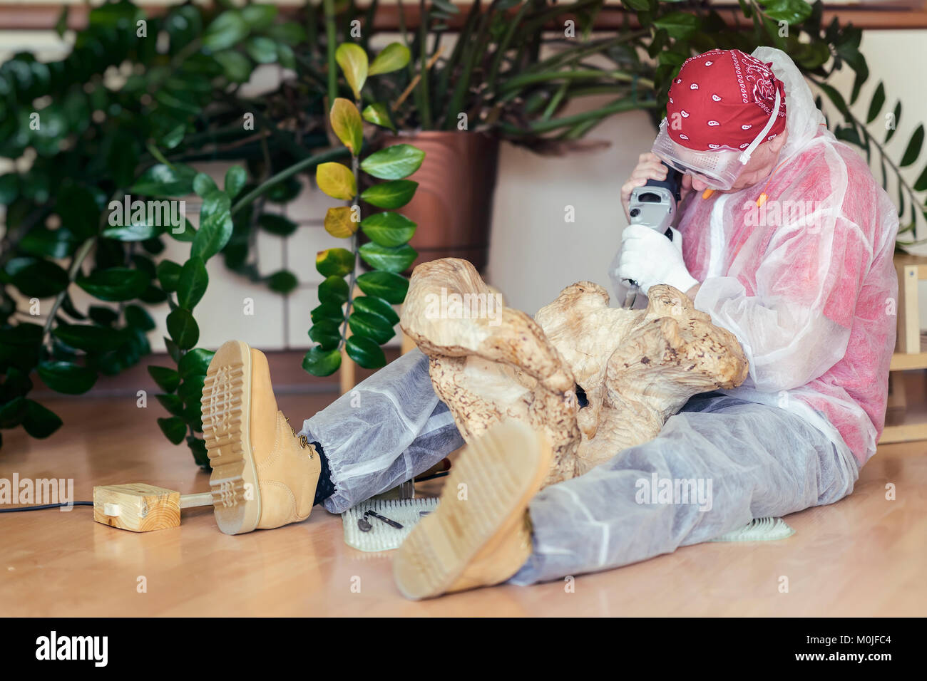 Man woodcarver carving from natural wooden stump, precious wood, art object for decorating house. Concept of handmade, - Stock Image