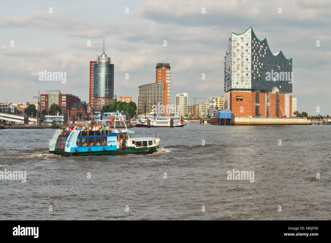 HANBURG, GERMANY- AUGUST 12, 2015: Boat with tourists goes on Elbe river towards Elbphilharmonie, a concert hall - Stock Image