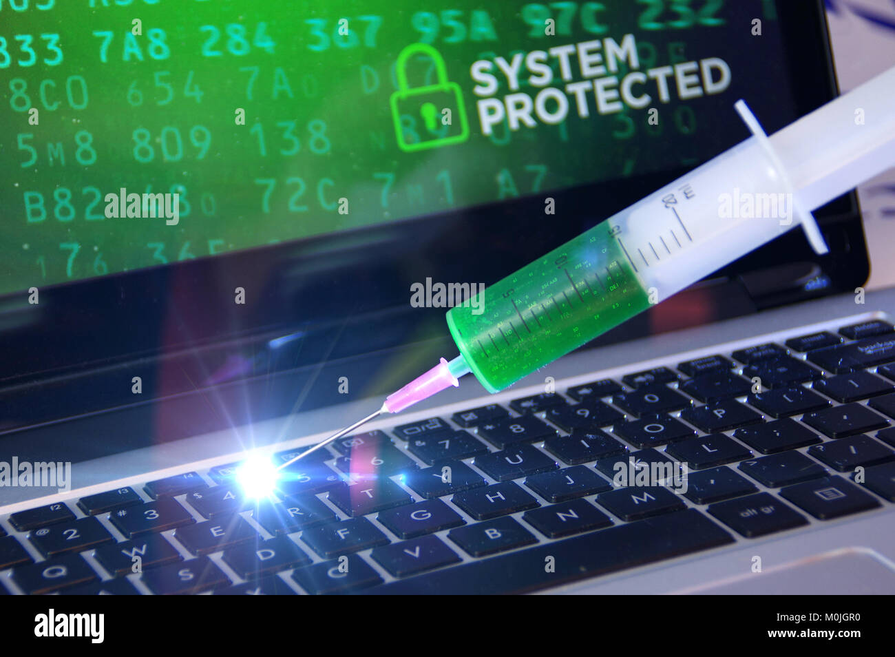 System protection concept and cybersecurity. Antivirus vaccination in the syringe applied to the computer. - Stock Image