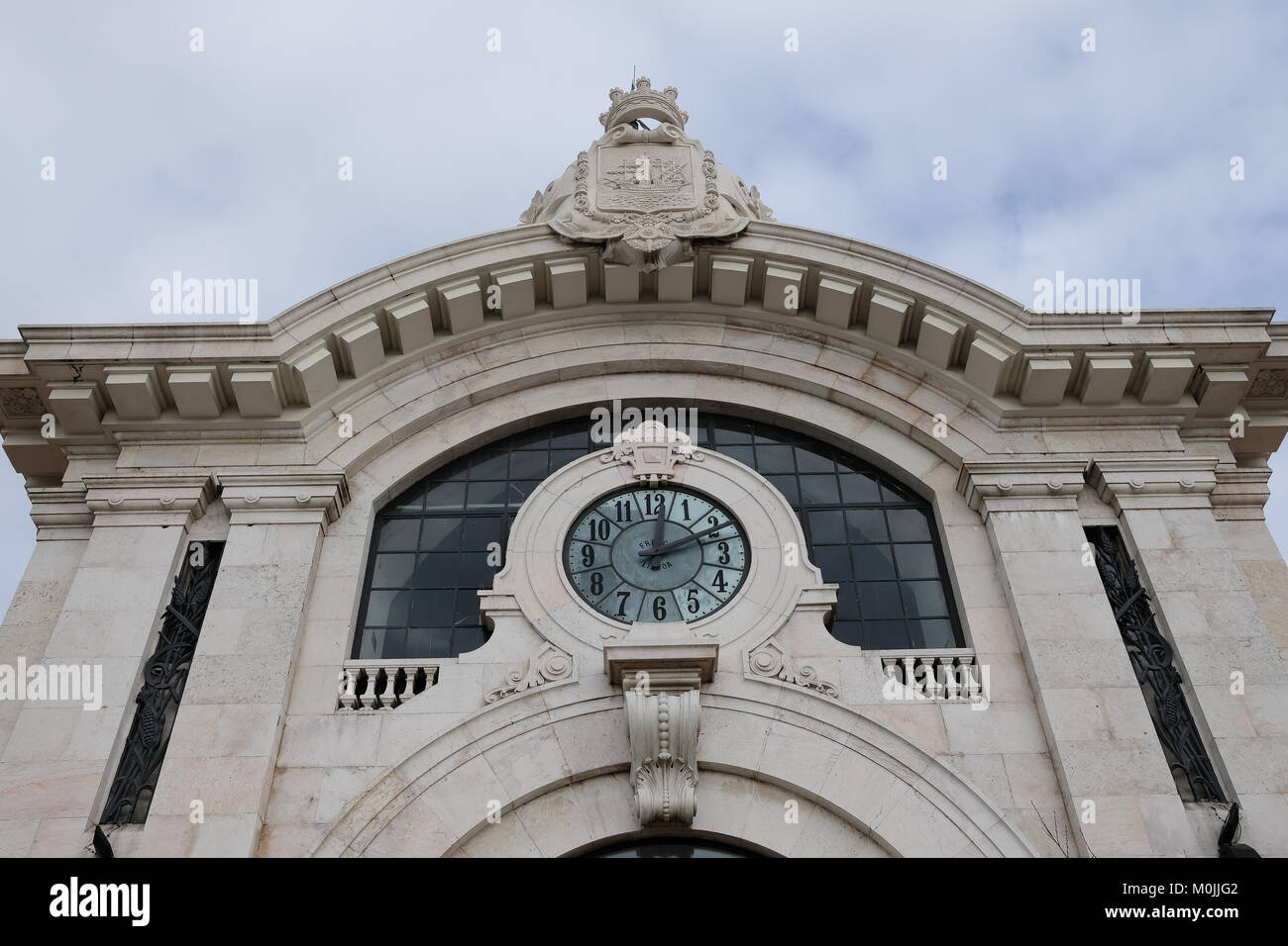 faced of the municipal market of Lisbon, Portugal showing a huge clock on it, lookup view - Stock Image