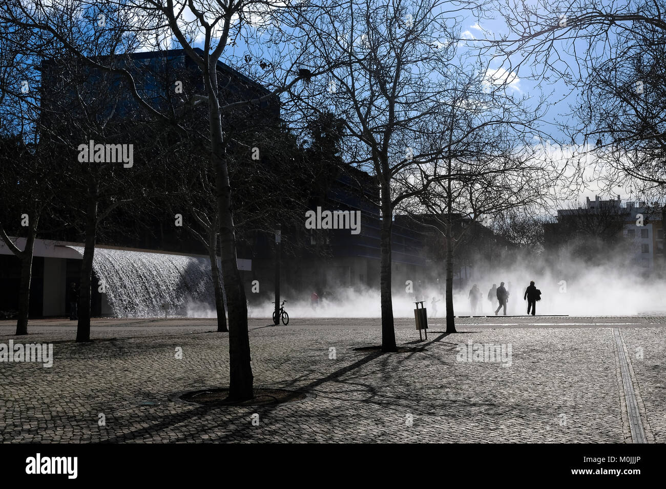 people walk trough a vapor fountain placed in one of the many public parks of Lisbon - Stock Image