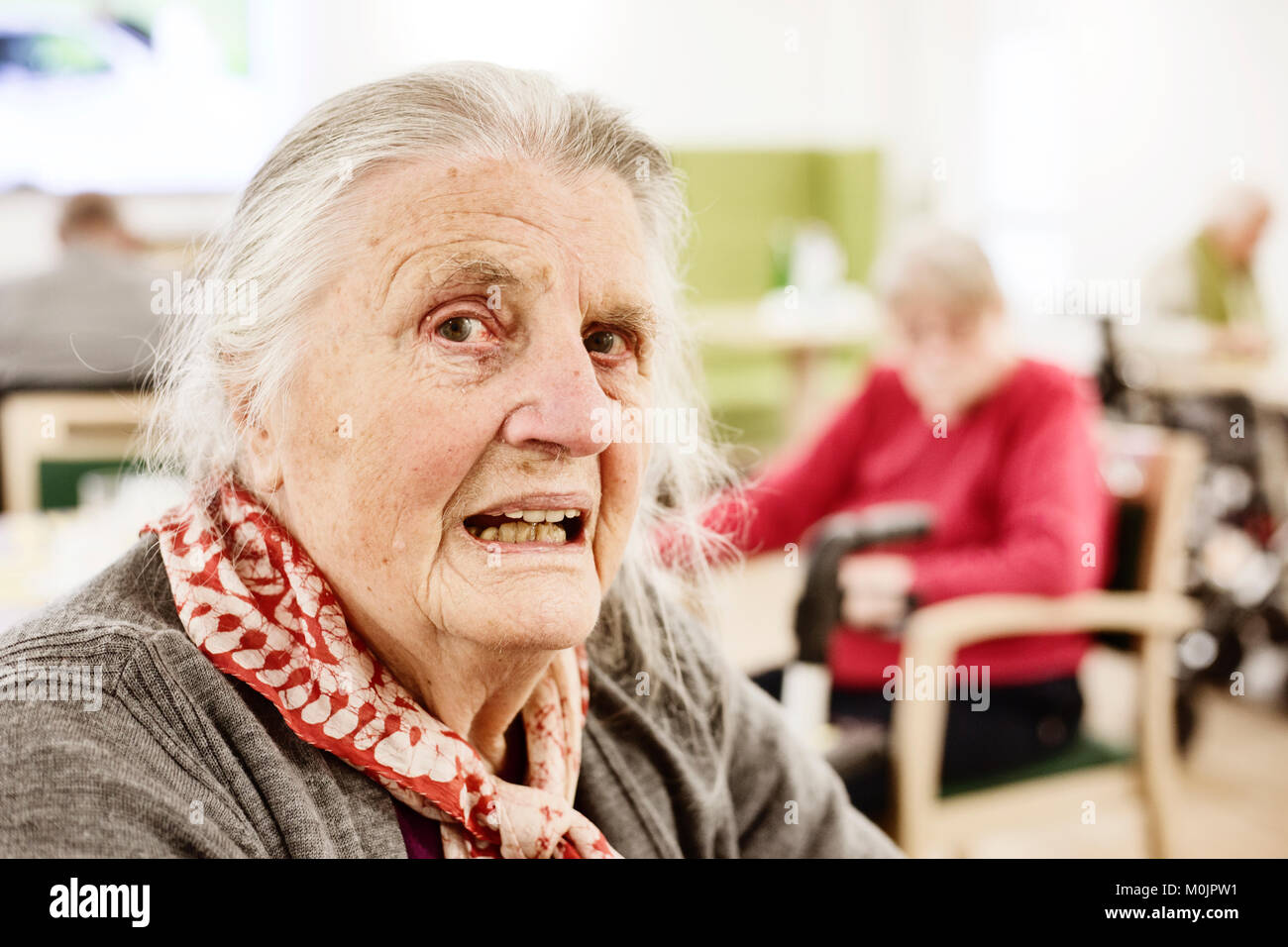 Demented senior citizen, portrait, looking questioningly, in a retirement home, Germany - Stock Image