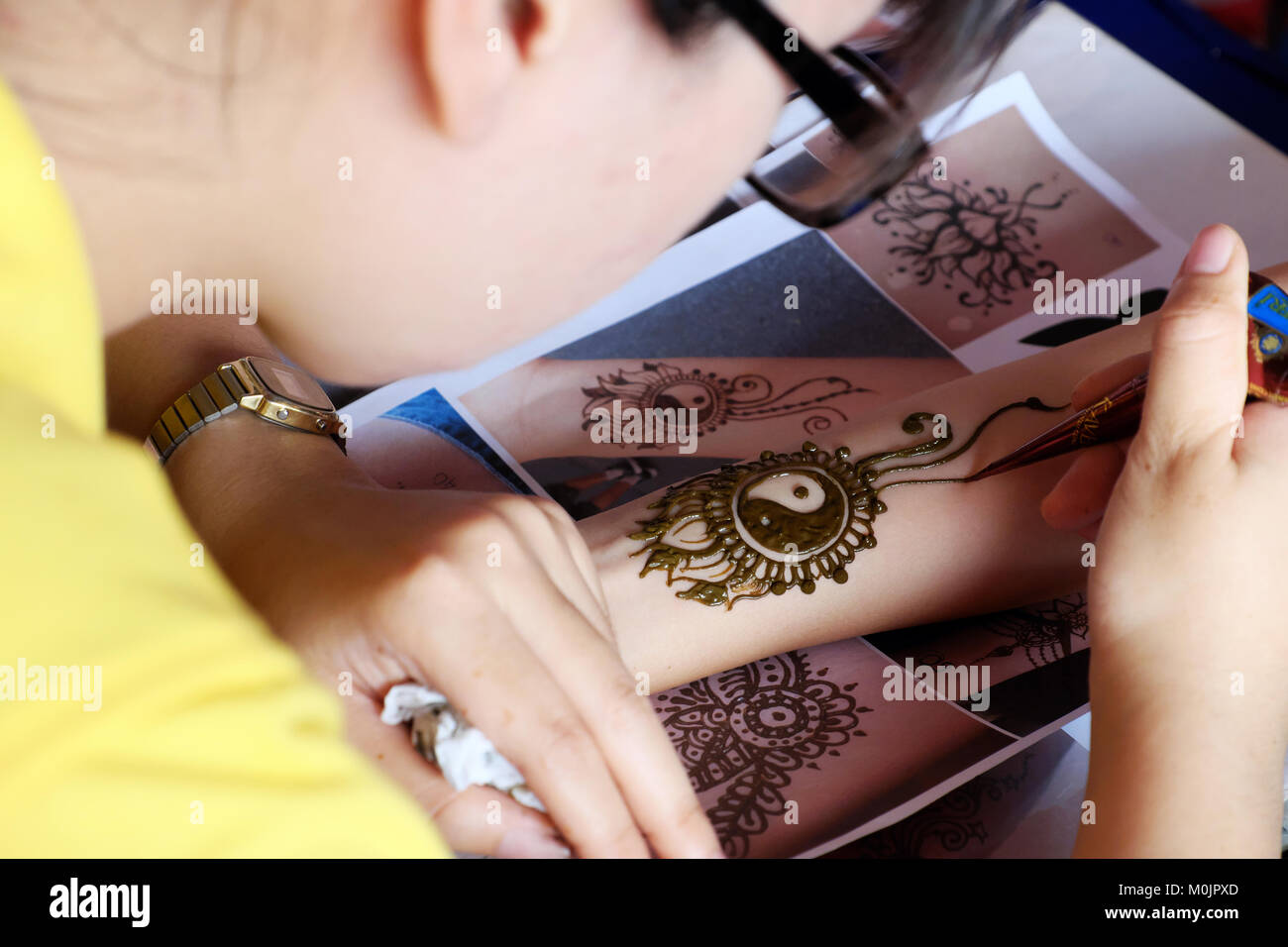 Artist drawing henna pattern on woman hand, a tradition art