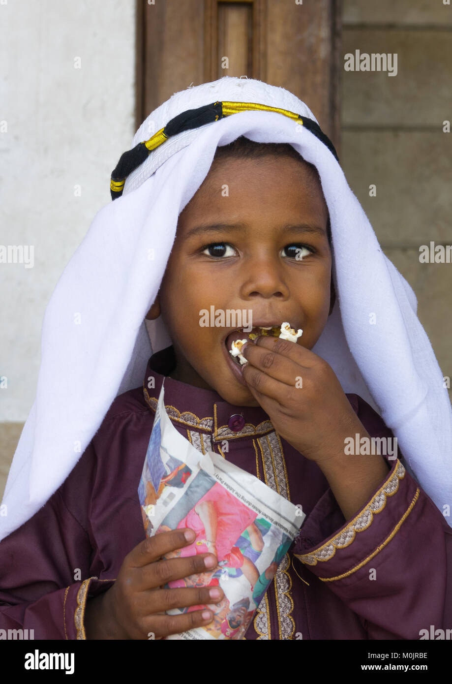 Young boy in traditional suit dressed for the Mawlid festival, eating popcorn, Lamu Island, Kenya - Stock Image