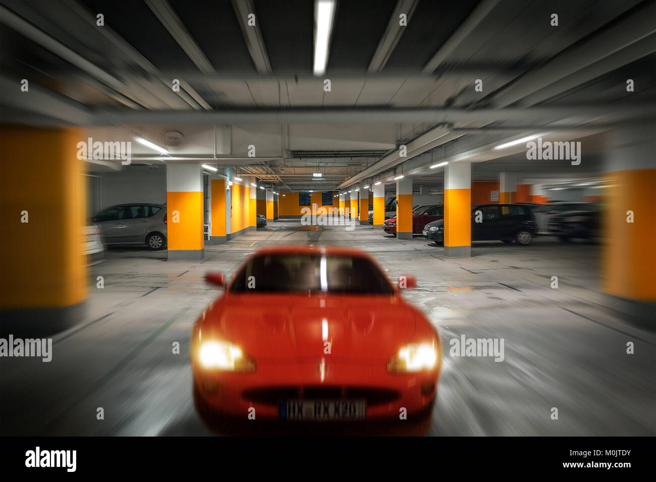 Car drives in underground garage, Germany - Stock Image