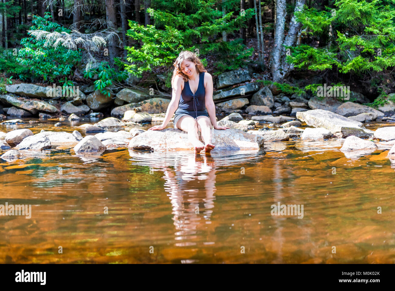Young happy smiling woman enjoying nature on peaceful, calm Red Creek river in Dolly Sods, West Virginia during - Stock Image