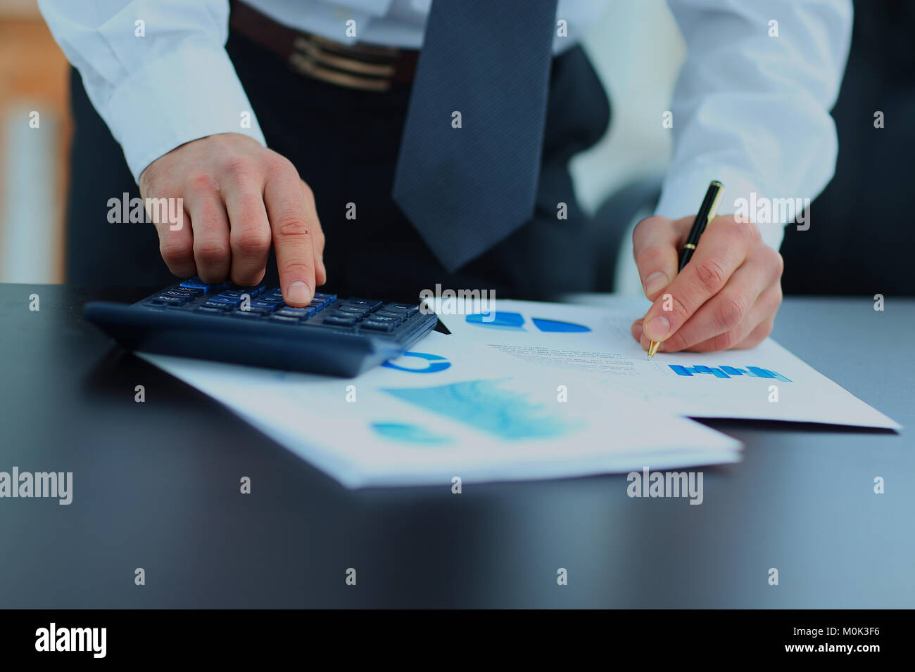 Businessman Using Calculator In Office. - Stock Image