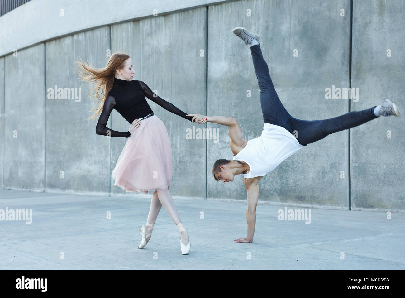 A young couple in love passionately dances on a city street. Dancer and sportsman Parkour. Balance and stunts in Stock Photo