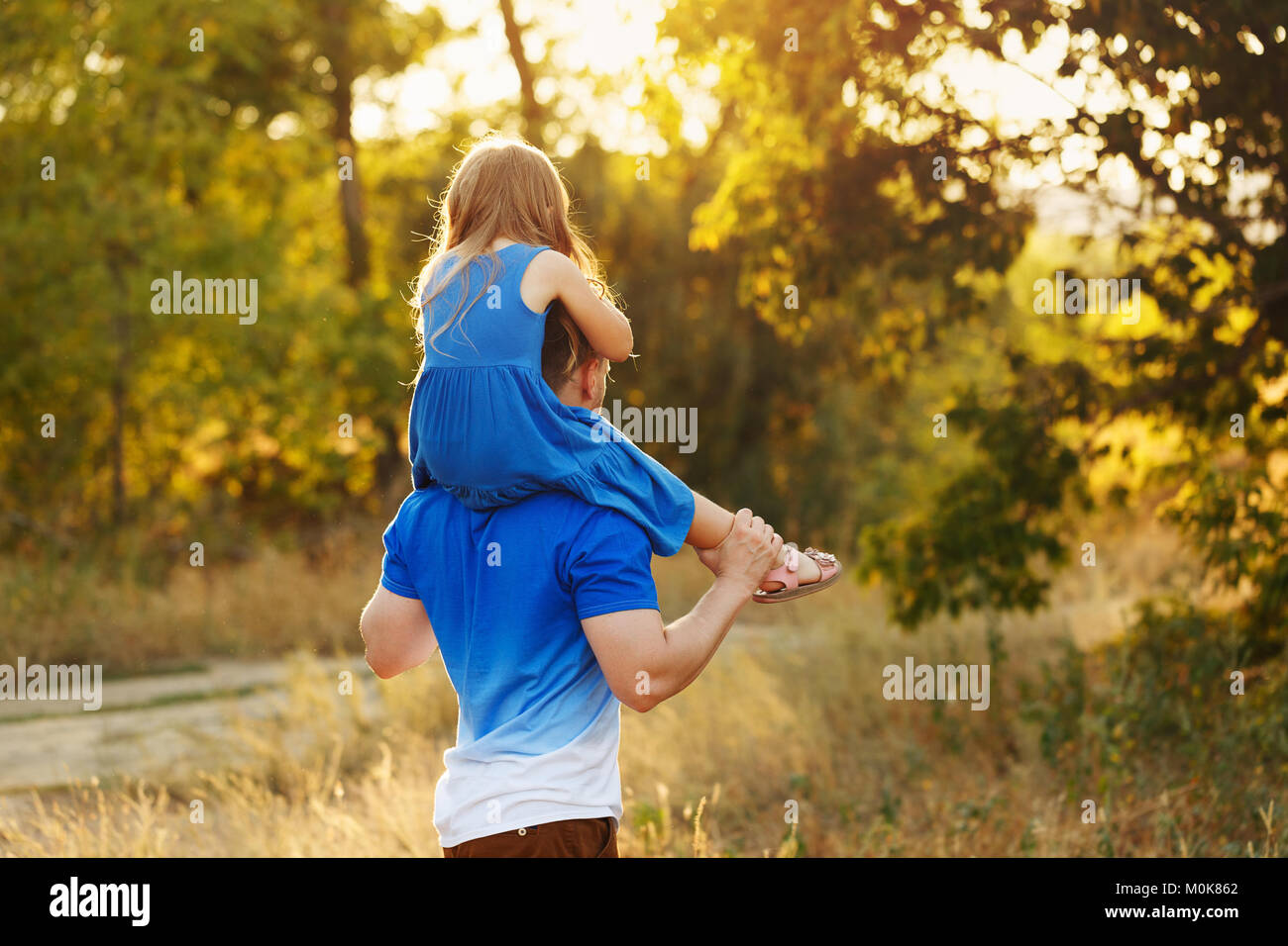 Father carrying daughter piggyback. Family holiday. A walk in the city park at sunset - Stock Image