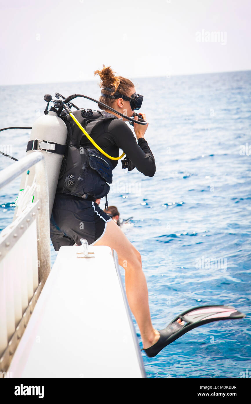 Female diver doing giant stride off dive boat; Negril, Jamaica - Stock Image