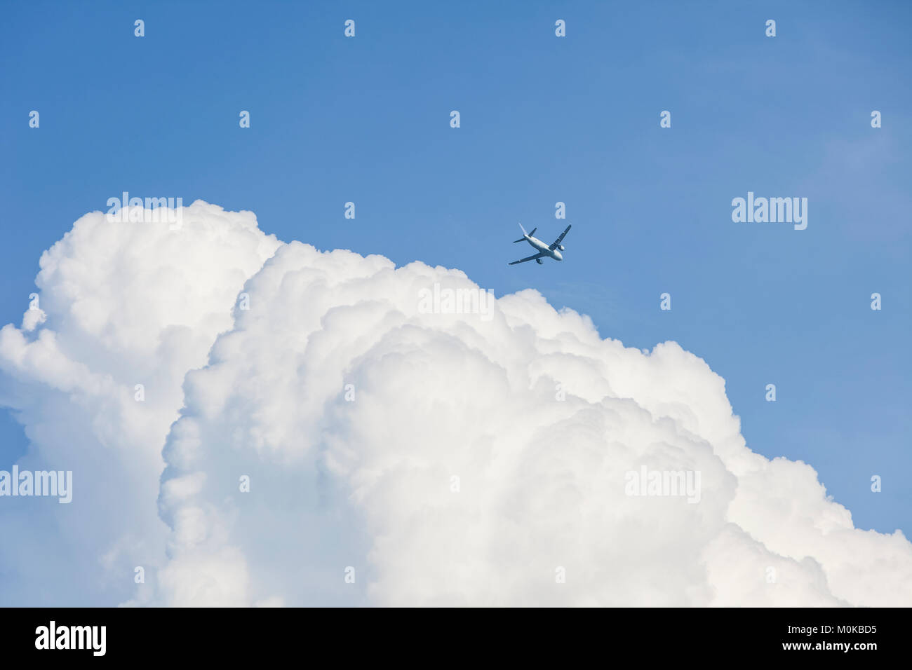 Commercial airliner and bank of clouds in a blue sky; Georgetown, Ontario, Canada - Stock Image