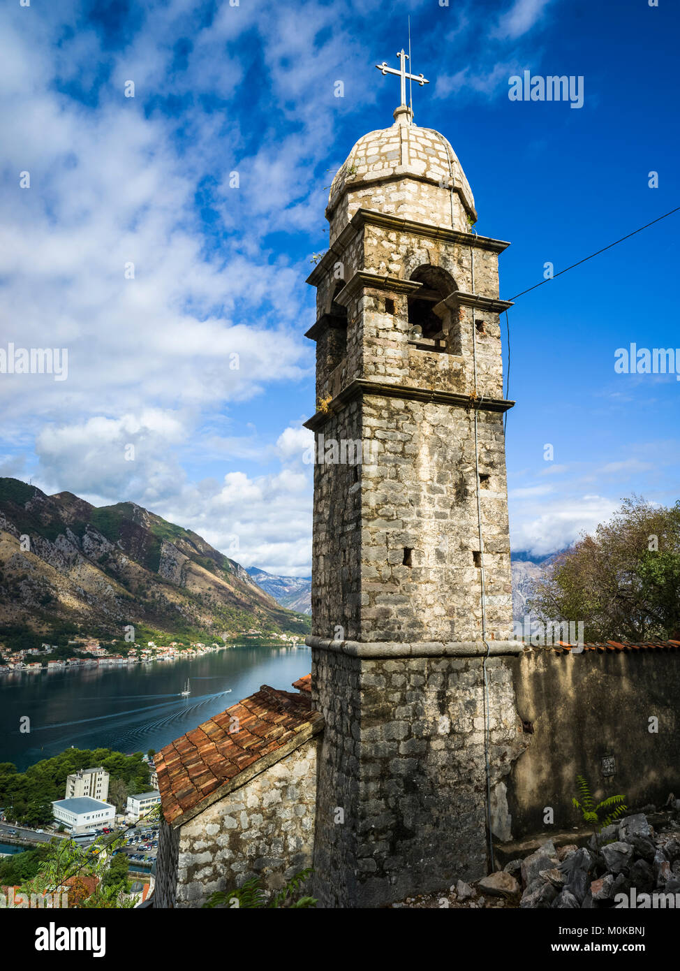 A stone tower with cross at Kotor Fortress and a view of the Gulf of Kotor; Kotor, Montenegro - Stock Image