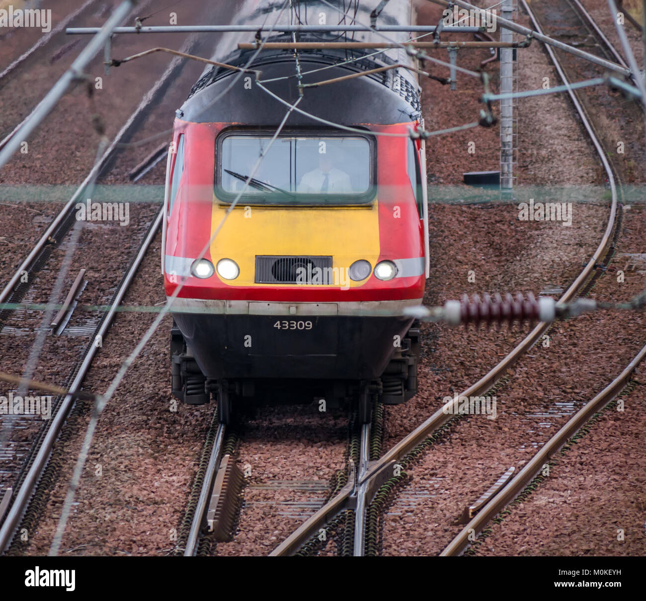 Zoomed view of Virgin train engine approaching Drem Station, with overhead cables, East Lothian, Scotland, UK - Stock Image