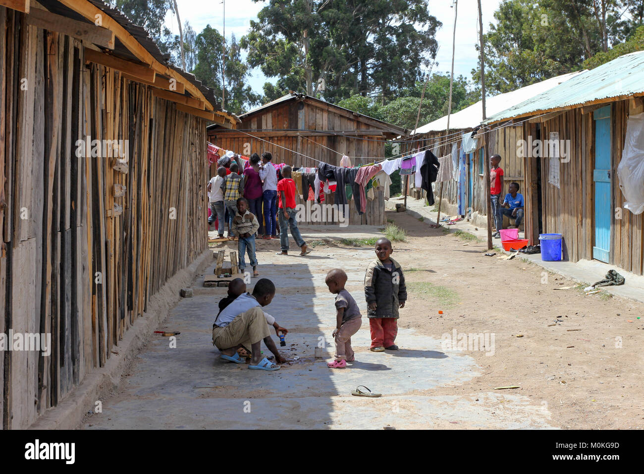 Candid scene looking down a residential street of locals playing and gathering in Nanyuki, Africa - Stock Image