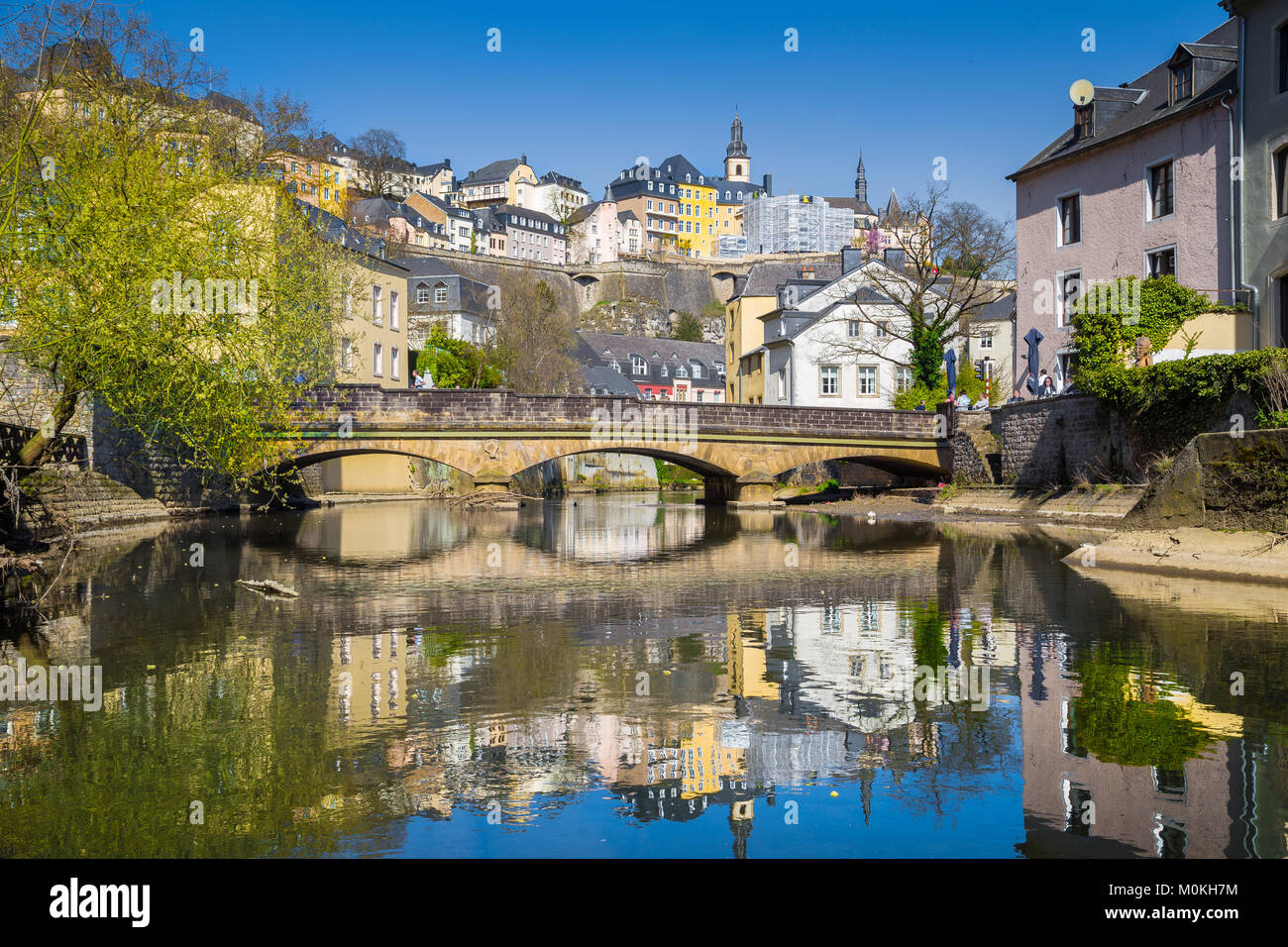 Classic view of the famous old town of Luxembourg City reflecting in idyllic Alzette river on a beautiful sunny - Stock Image