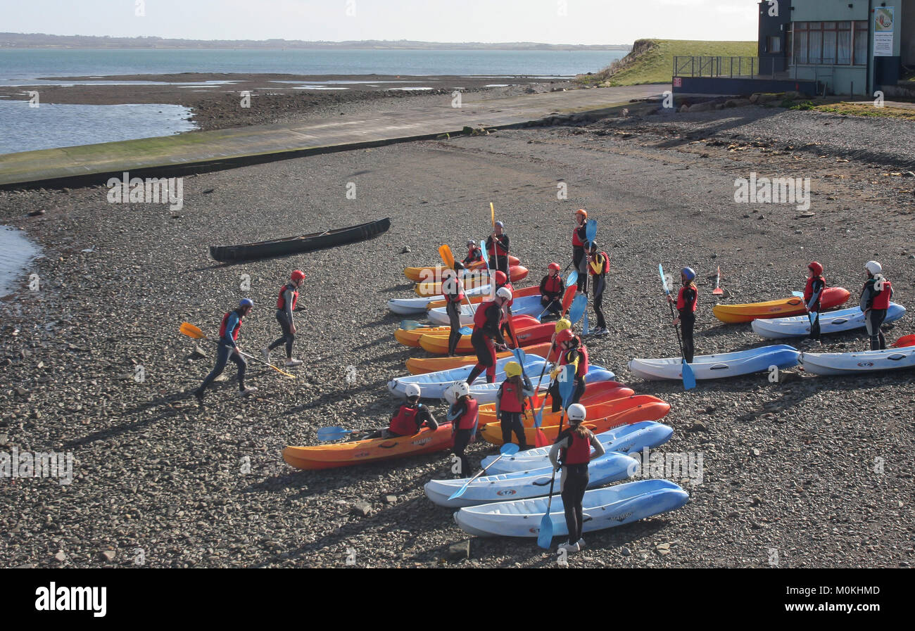 Teaching kayaking in Ireland. Children learning to kayak on a stoney beach at Carlingford, County Louth Ireland. - Stock Image