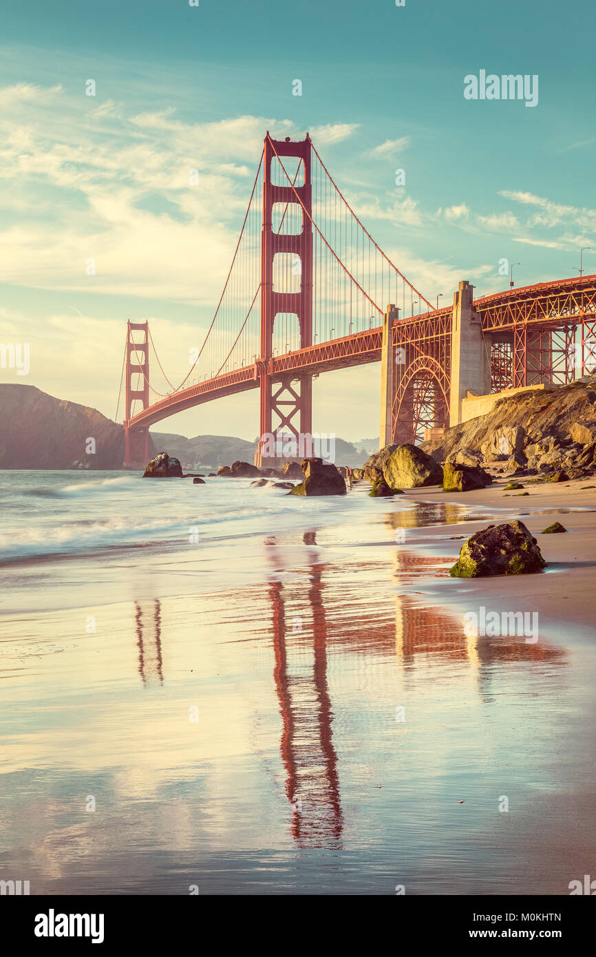 Classic vertical view of famous Golden Gate Bridge seen from scenic Baker Beach in beautiful golden evening light - Stock Image