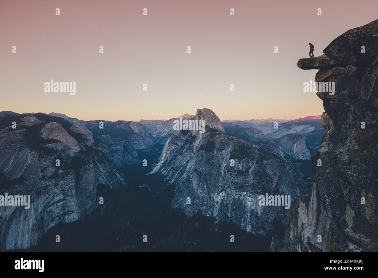 A fearless hiker is standing on an overhanging rock looking towards famous Half Dome in Yosemite National Park in - Stock Image