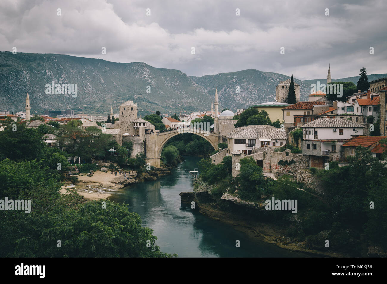 Classic view of the historic town of Mostar with famous Old Bridge (Stari Most) on a rainy day with dark clouds - Stock Image