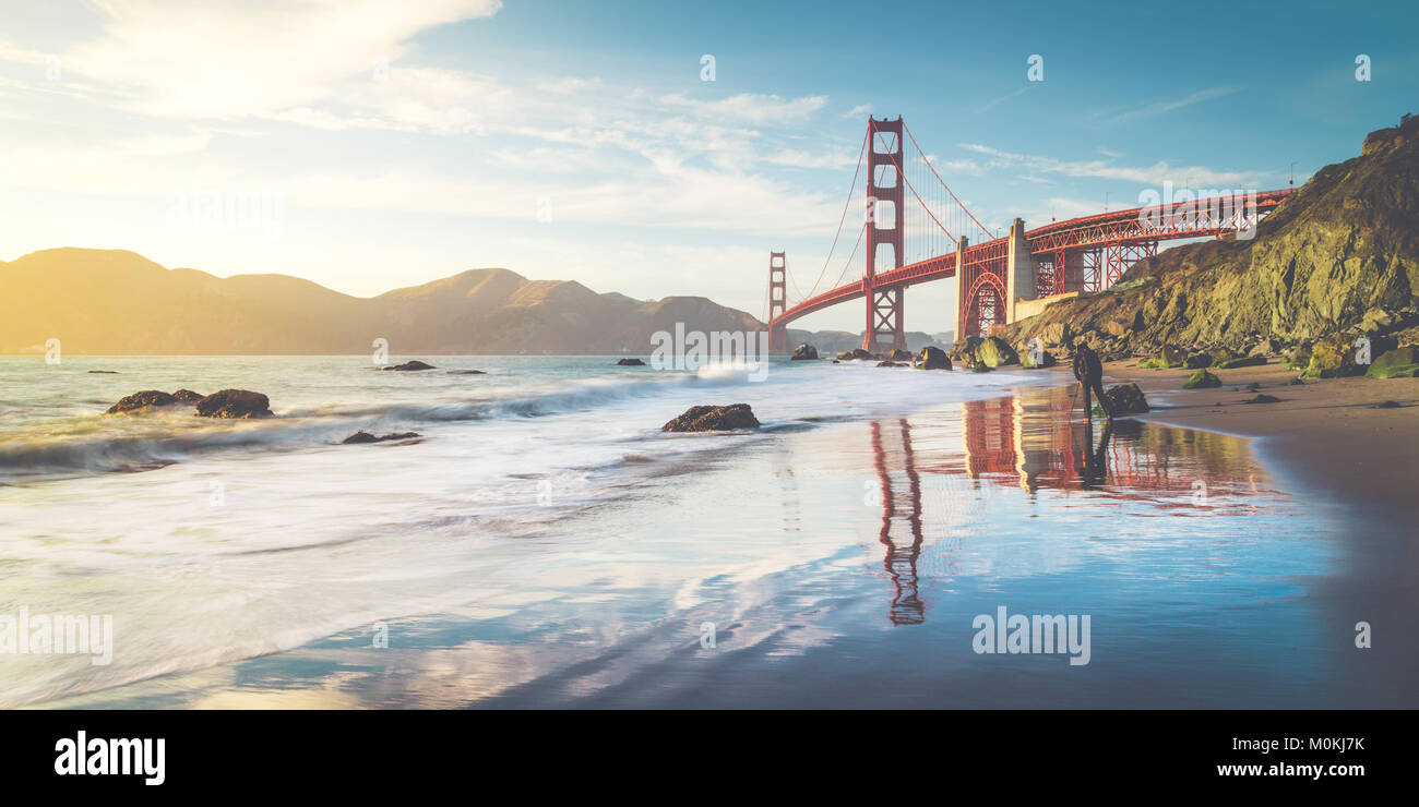 Classic panoramic view of famous Golden Gate Bridge seen from scenic Baker Beach in beautiful golden evening light - Stock Image