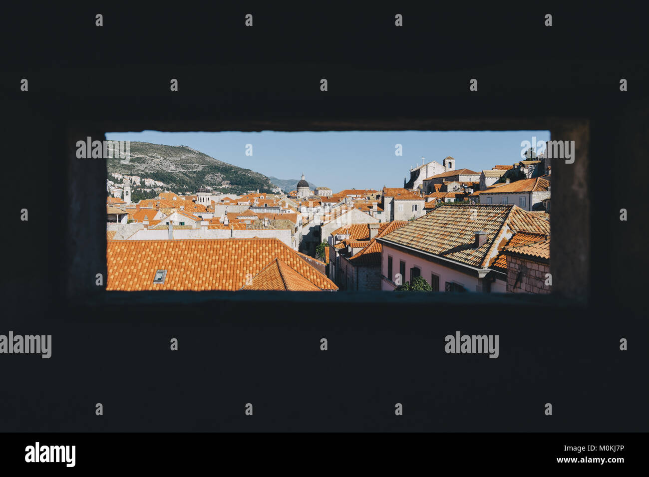 Looking out of a window at red colored terra-cotta rooftops in the historic town of Dubrovnik in beautiful evening - Stock Image