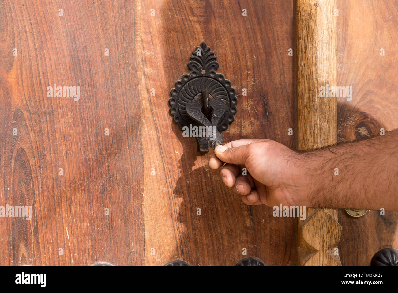 Wooden door with knocker types and decorated buttons, Masuleh village, Gilan province, Iran - Stock Image