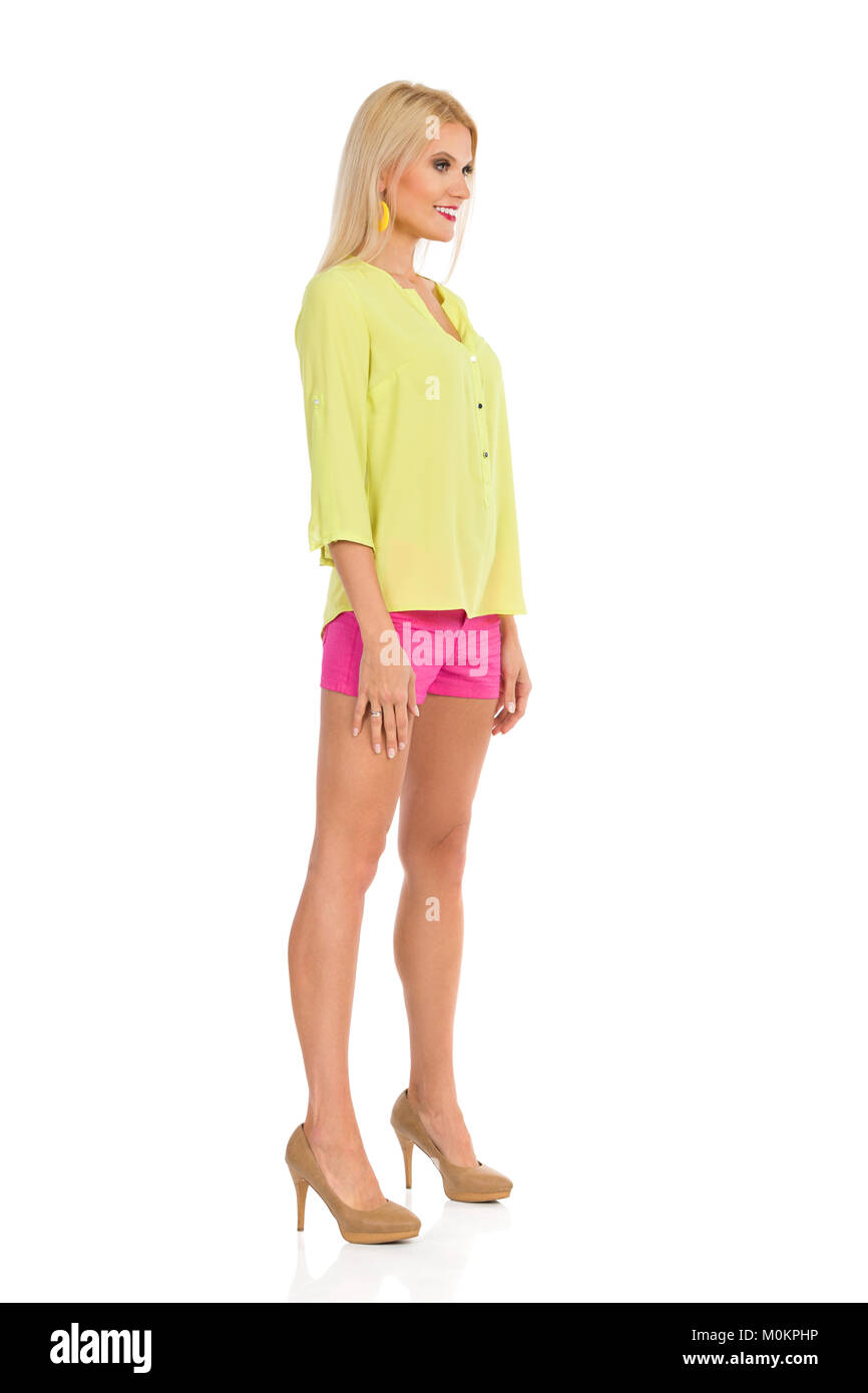 Beautiful blond woman in pink shorts, yellow shirt and high heels is standing at attention and looking away. Side - Stock Image